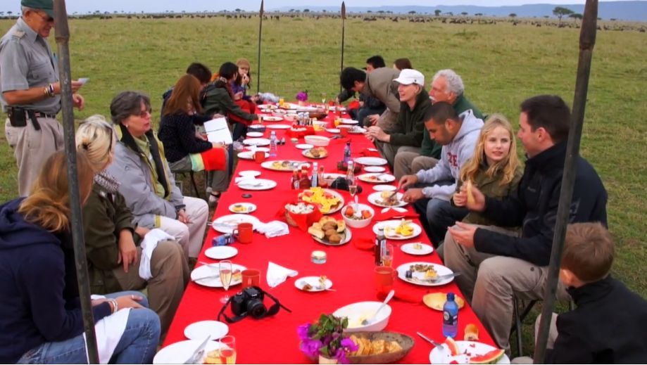 Australian tourists eating tasty African native traditional food on travel holiday tour balloon safari in Kenya